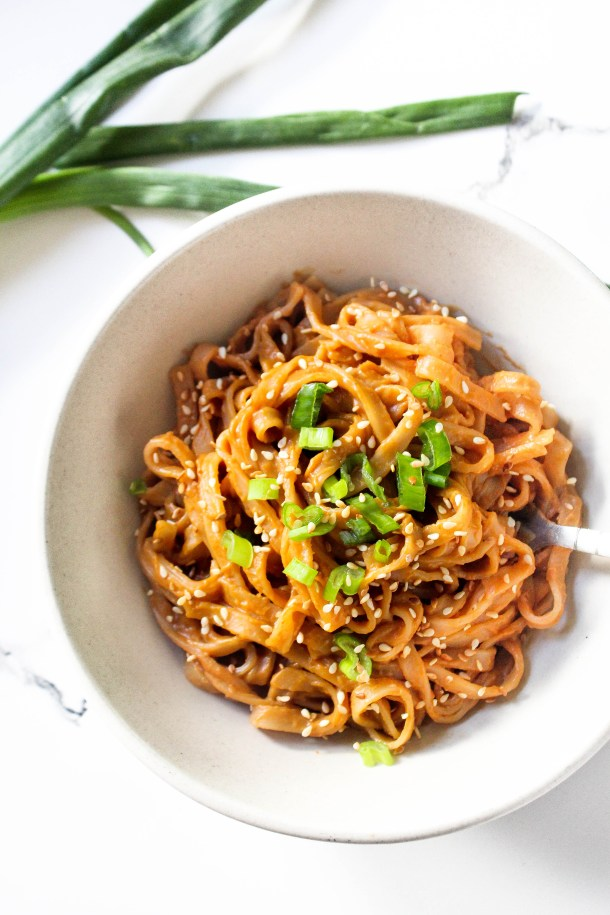 Flat rice noodles tossed in an orange brown peanut sauce topped with white sesame seeds, served in a white bowl, placed on a white tile.