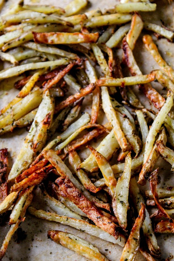 Golden thin cut brown crunchy and crispy potato french fries that are baked and tossed in garlic butter with green dried parsley served on a brown sheet on baking tray