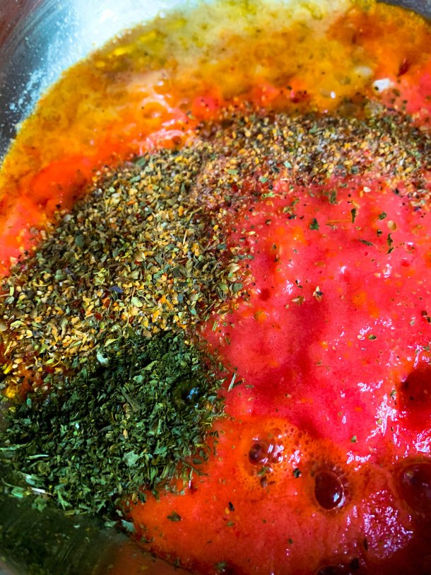 tomatoes, parsley, oregano, salt, pepper, sugar, butter and garlic in a pan to make homemade pizza sauce.
