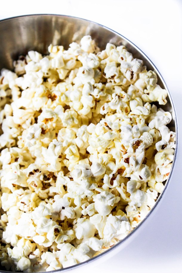 White puffed and popped pop corn in a bowl on a white tile.