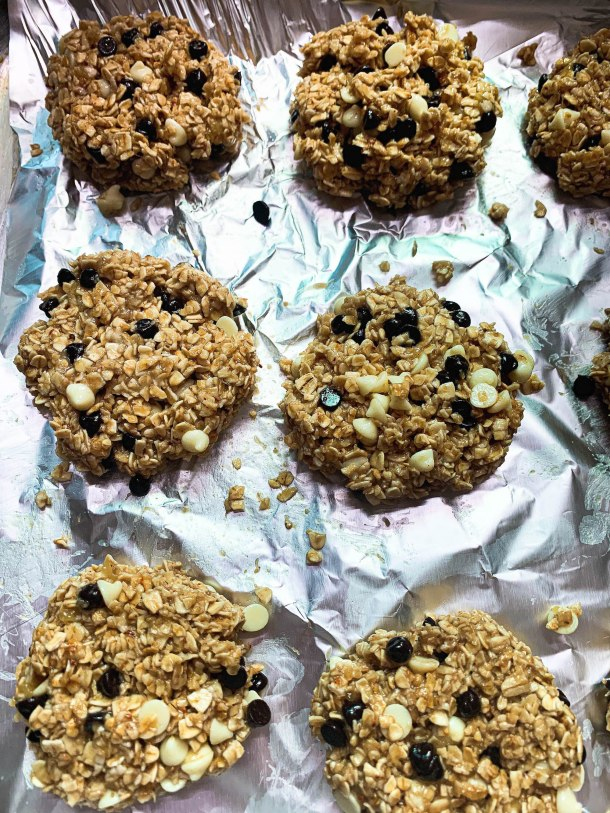 Brown crunchy and chewy oatmeal cookies with black and white chocolate chips on a baking sheet on a white tile.