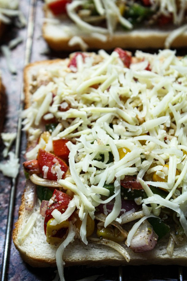 Toasted white bread topped with onions, tomatoes, sweet corn, capsicum and mozzarella and cheddar cheese, placed on a grill