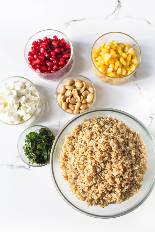 Quinoa salad with corn, pomegranate, peanuts, fresh mint leaves, paneer (indian cottage cheese) in a glass bowl on a white tile.
