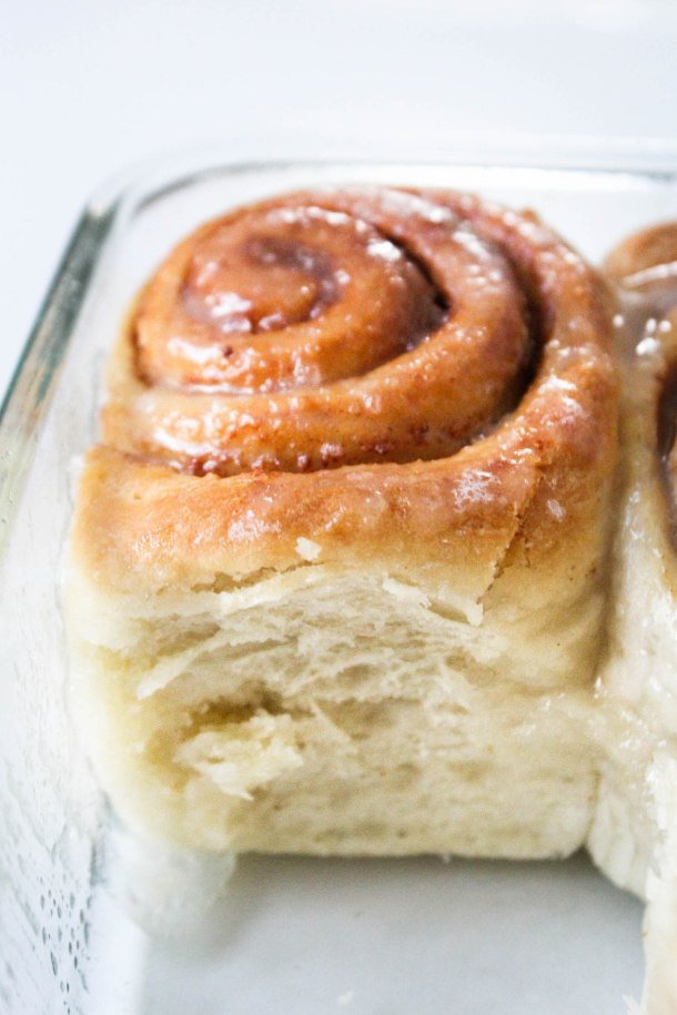 Soft and eggless cinnamon rolls in a glass dish on a white tile