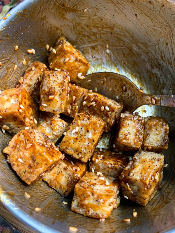 Crunchy oven baked tofu cubes tossed in sticky hoisin sauce and sesame seeds - in a large mixing bowl.
