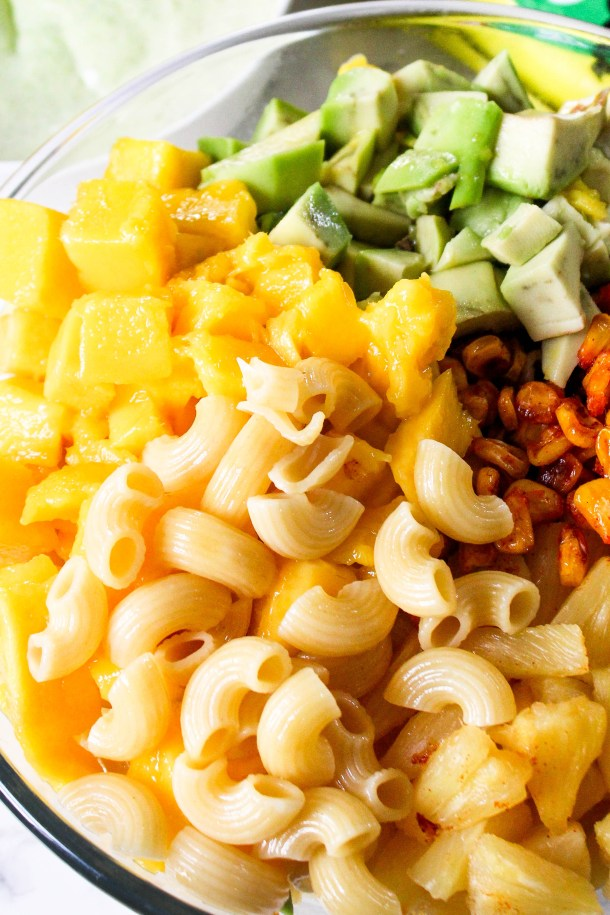 Mango Avocado Summer Macaroni Pasta Salad with grilled Corn and Pineapple in a large bowl on a white tile