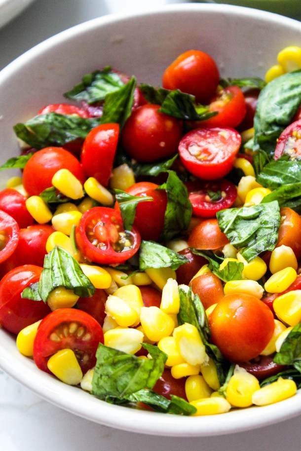 cherry tomato, corn and basil in a bowl