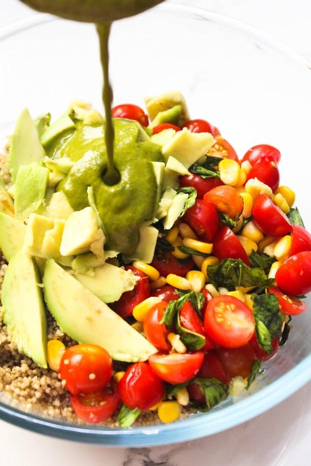Sweet Corn, Cherry Tomato, Avocado Quinoa Salad with homemade lemon basil vinaigrette in a glass bowl.
