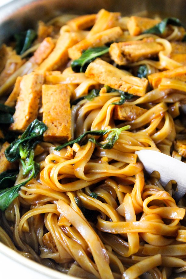 Red Brown Rice noodles coated in a vegan sauce mixed with basil and topped with crunchy tofu strips, served in a frying pan.