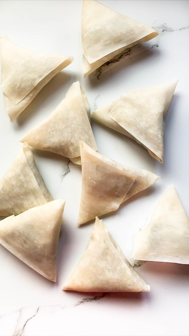 Sweet potato samosas wrapped and placed on a white tile