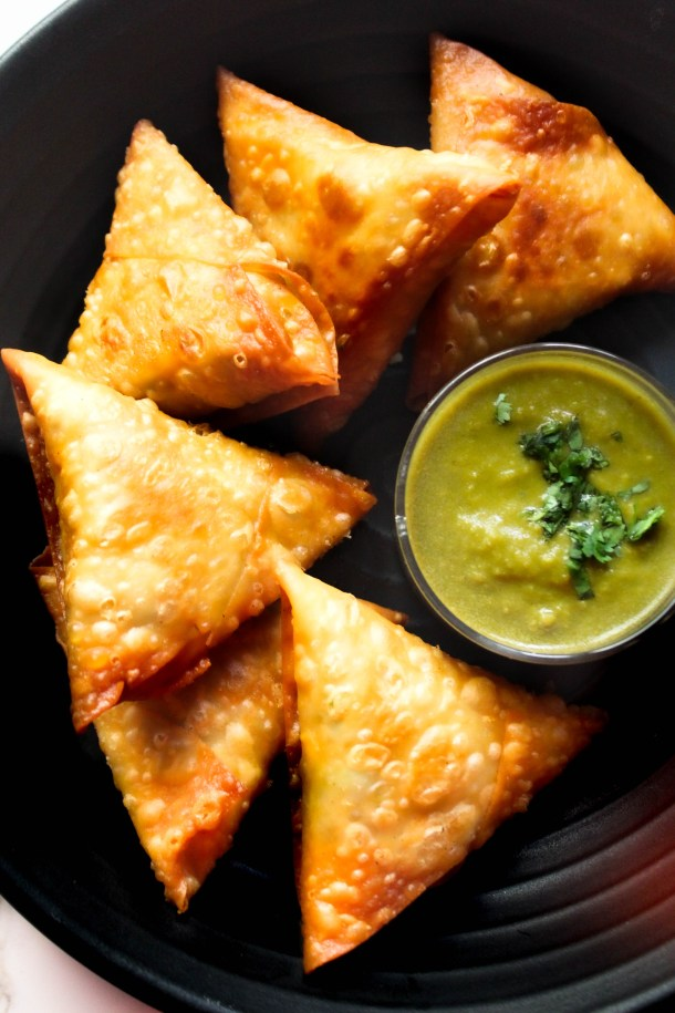 Crunchy bite sized mini samosas filled with sweet potato and peas, placed on black dish with green coriander chutney in a small glass bowl