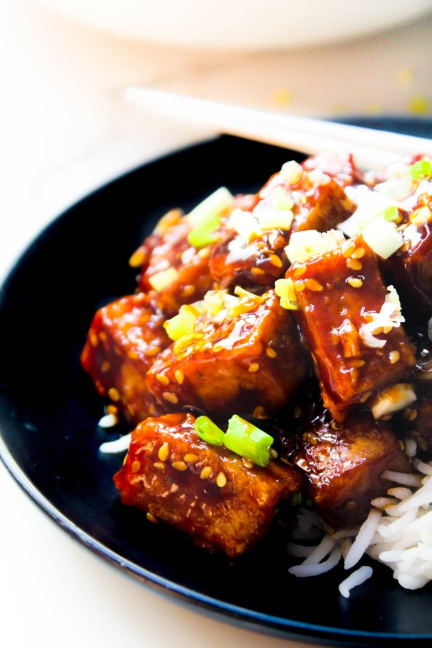 Reddish Brown Sticky Sesame Crispy Tofu served on white rice served in a black plate and placed on a white tile.