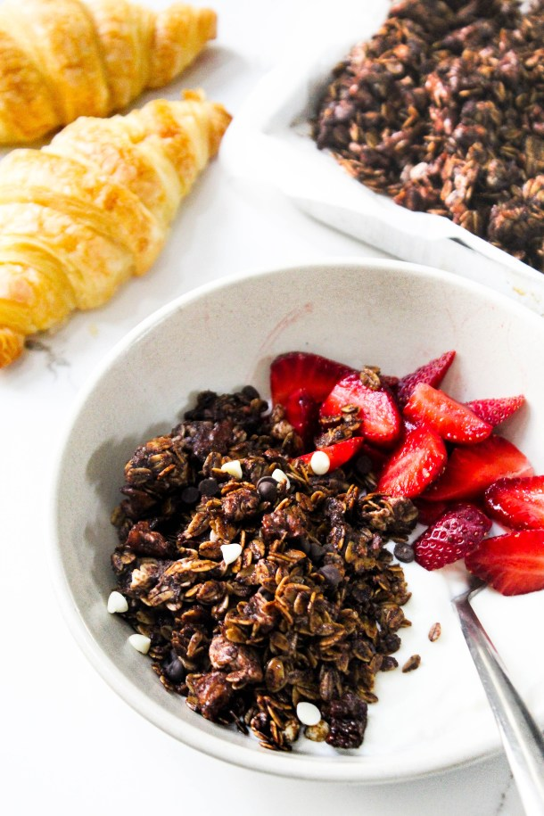 Crunchy homemade chocolate and walnut granola over yogurt with fresh cut red strawberries in a large bowl. Croissants in background.