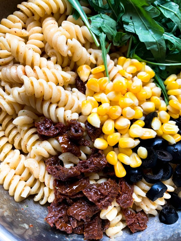 Mascarpone Pasta with red sun dried tomatoes, yellow corn, fresh Arugula green leaves, black olives, placed in a bowl.