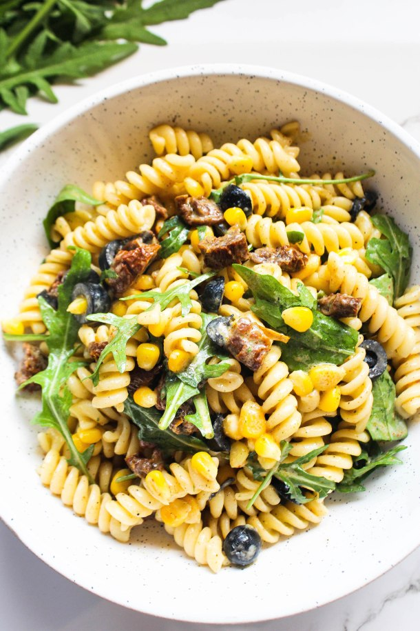 Mascarpone Arugula Pasta Salad with red sun dried tomatoes, yellow corn, fresh green leaves, black olives, placed in a white bowl on white tile.
