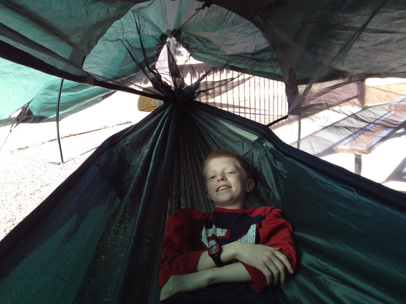 "My son posing in the hammock with the tent pole installed. He loved the additional head room and remakes that he could ""easily read a book"" in this hammock."
