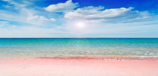 Serene beach scene with pink sand and sunny sky  How Natalie learned she has an allergy to cold (Cold Urticaria) and has adapted her life to be able to cope with it better.