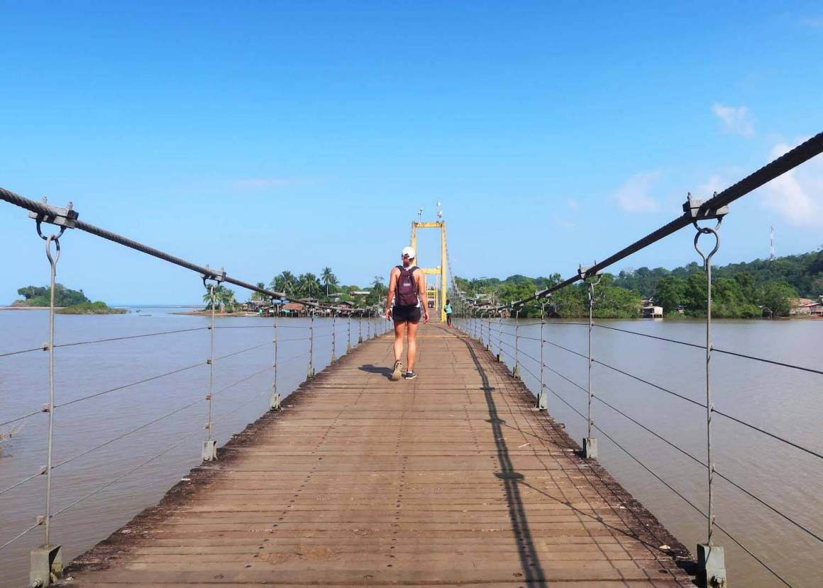 Kim walking on bridge over river