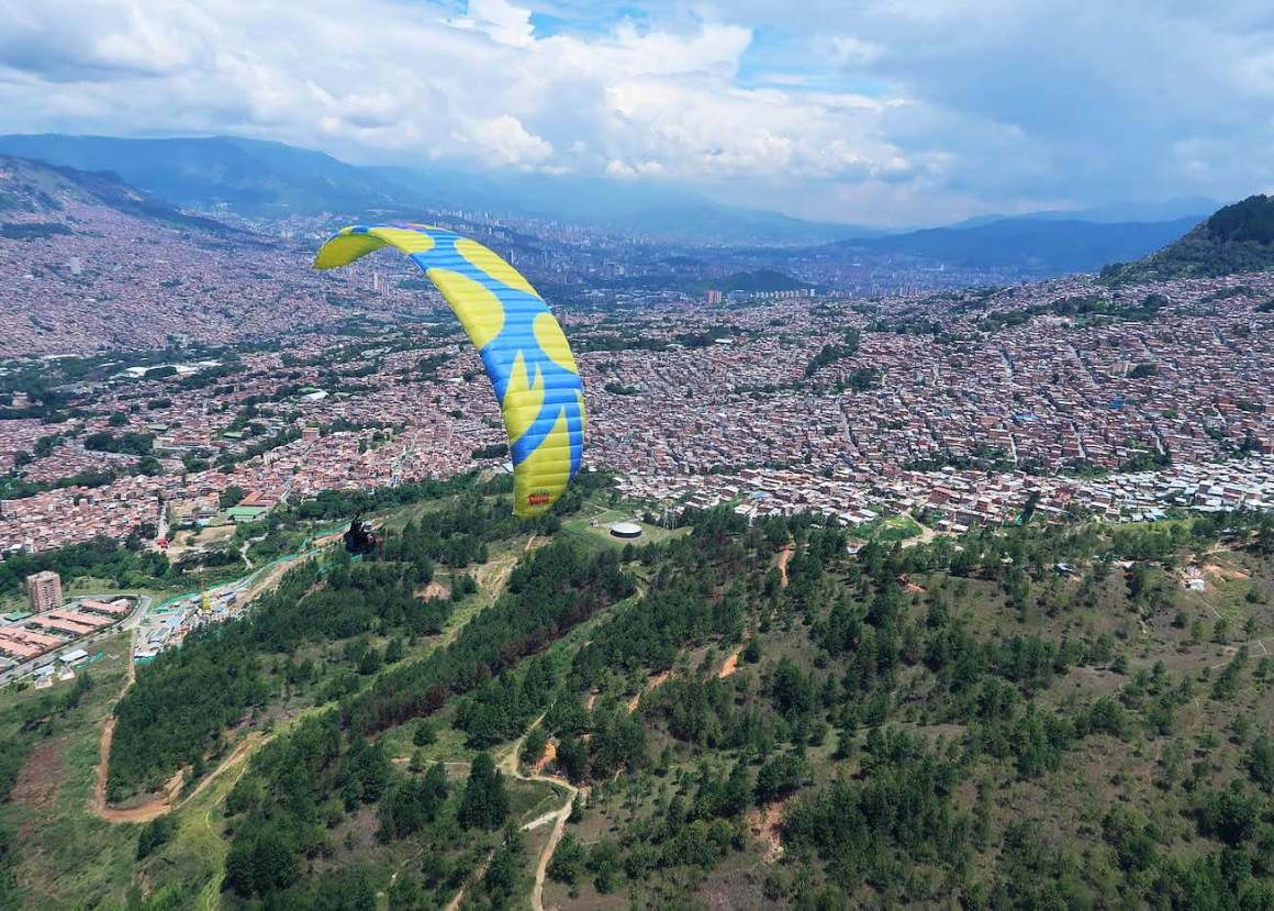 Another paraglider, with Medellin in background, circling down towards landing