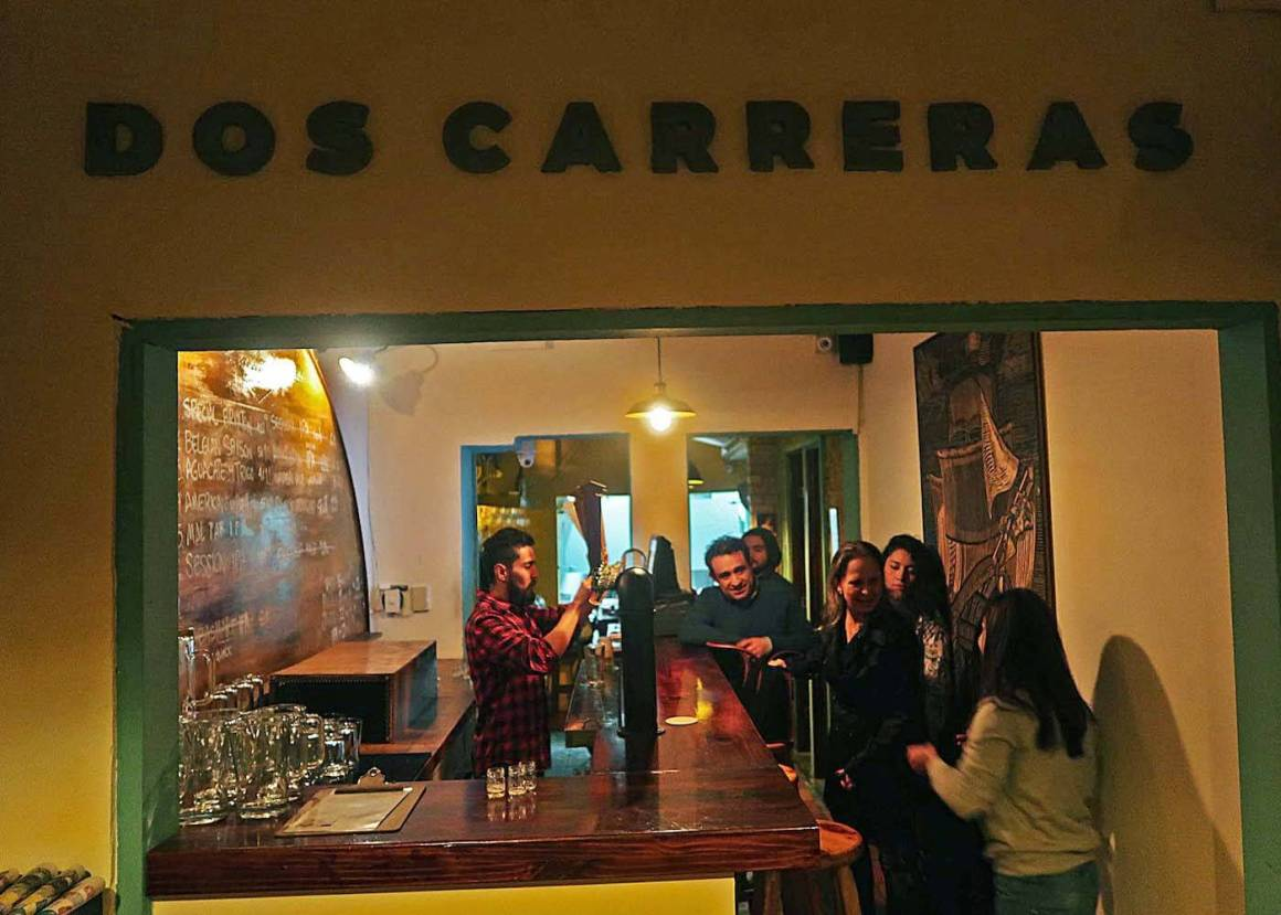 People at the bar and bartender at Dos Carreras microbrewery in Bogota