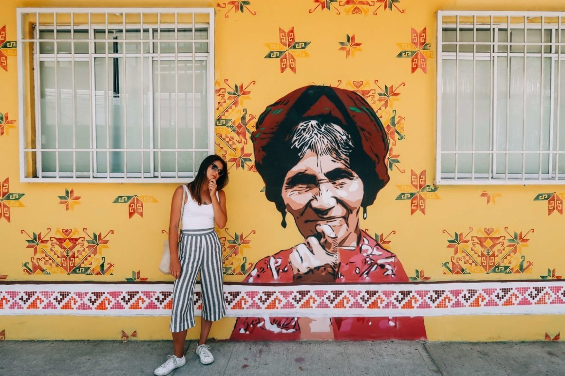 kim standing in front of a yellow mural in mexico city
