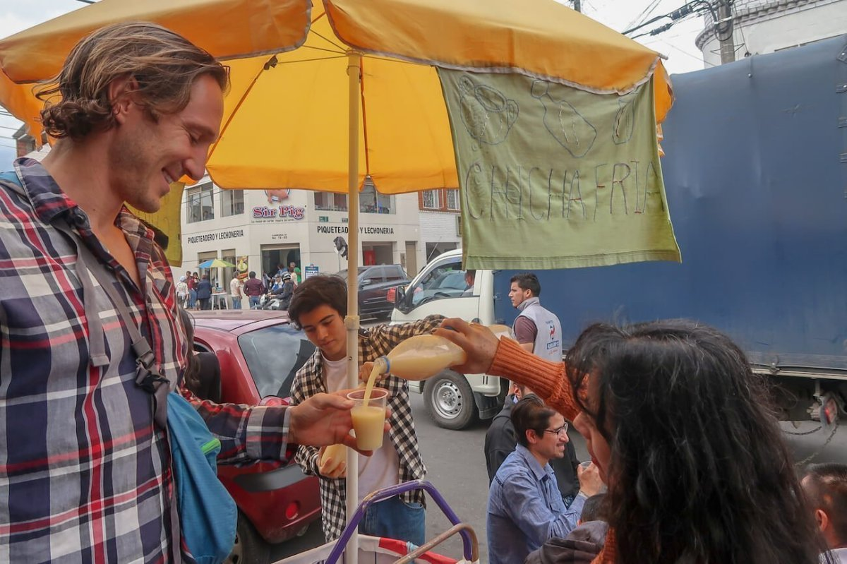 A street vendor pouring chicha, a traditional Colombian drink, for Chris