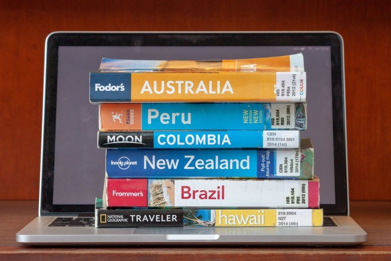 Travel guidebooks vs blogs cover image of travel guides stacked on top of a laptop