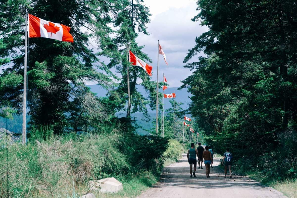 walking along savary island's beachfront with canadian flags