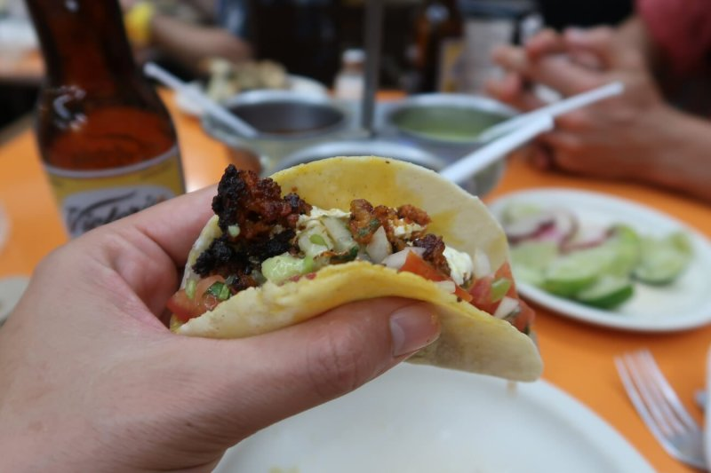 First person of eating a taco, one of the pros of traveling to Playa del Carmen