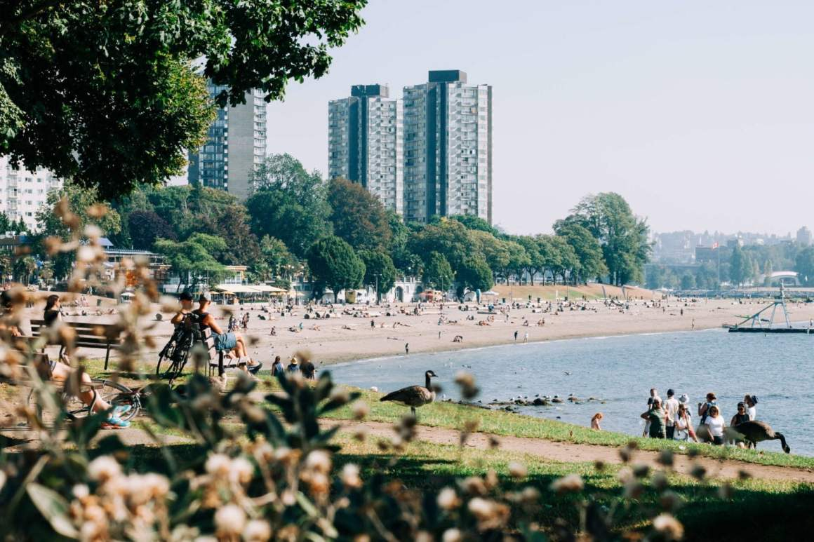 english bay beach and people sitting on benches