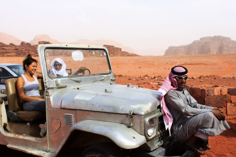 best travel tips and tricks cover image of Kim in jeep with locals in Jordan