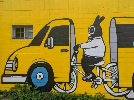 Street art of biker in car