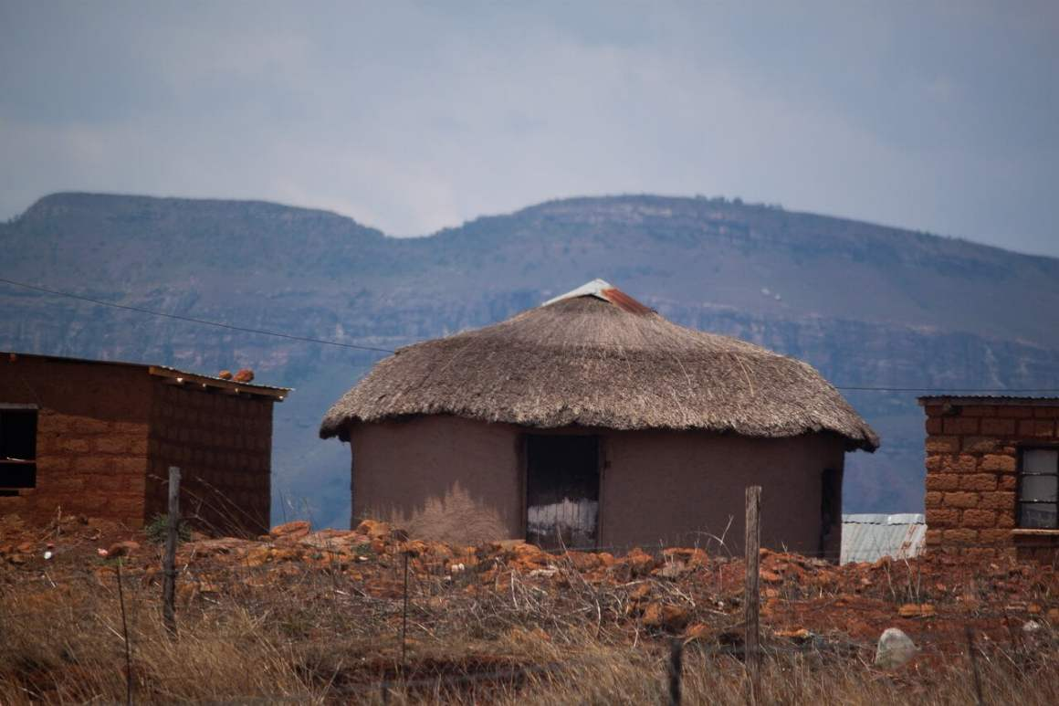 rural house made out of clay and thatched roof outside of drakensberg