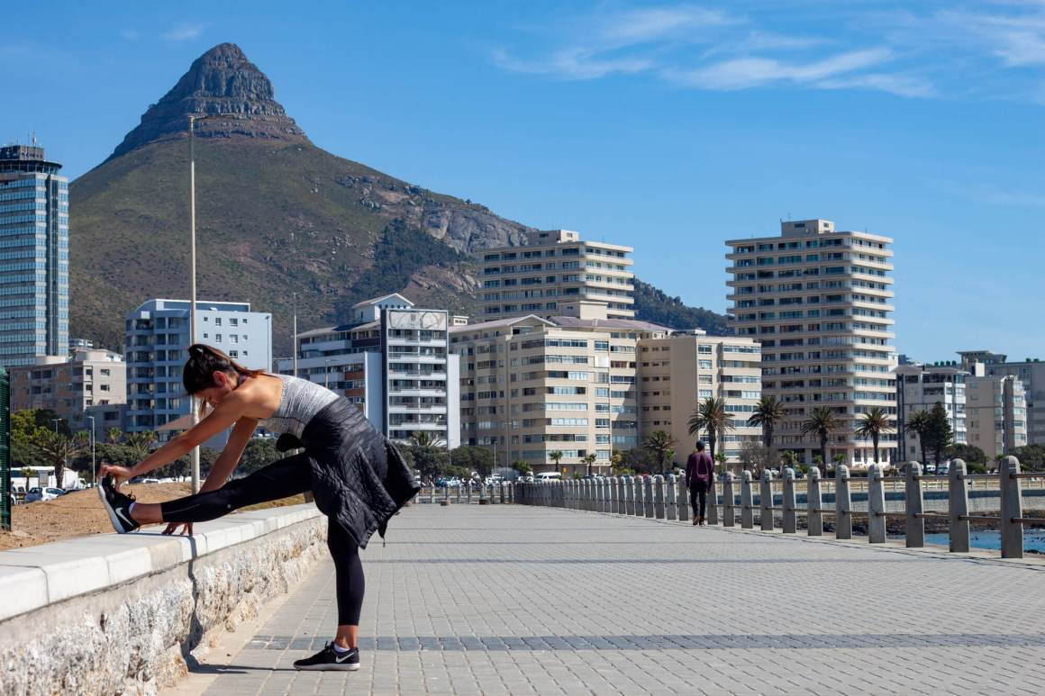 Kim stretching on Sea Point promenade with Lion's Head in background