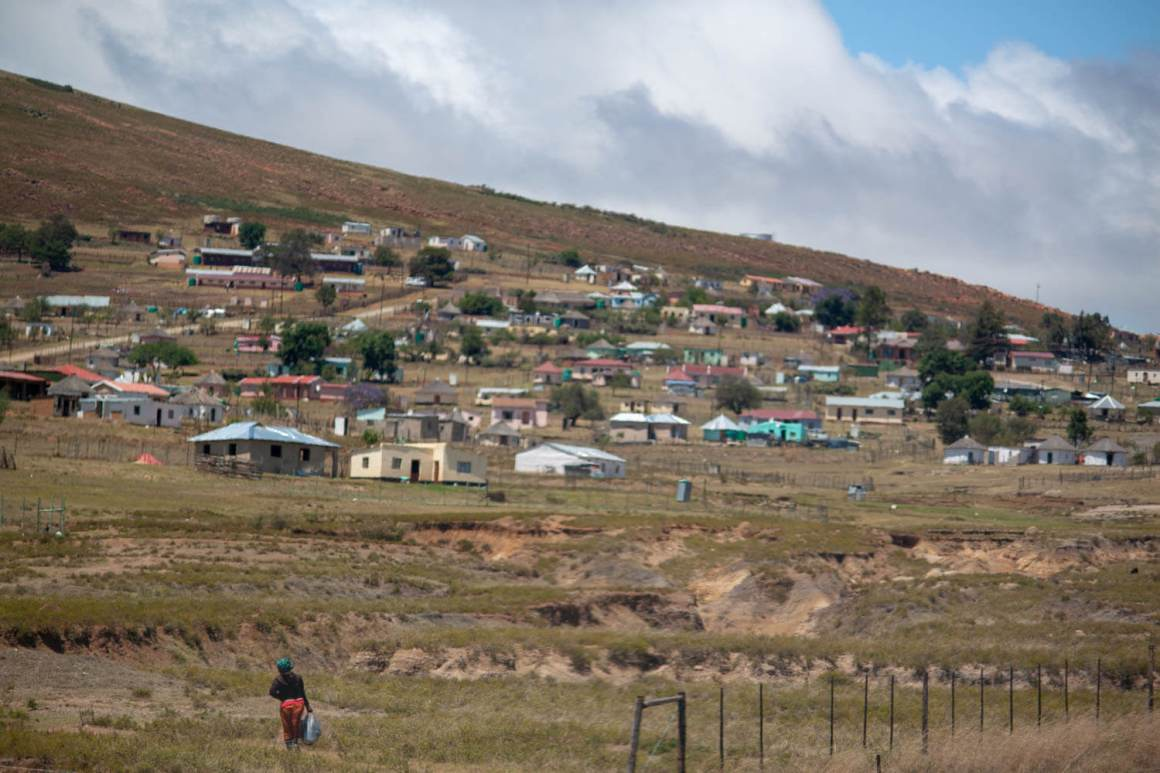 Lady walking towards rural houses in the Transkei