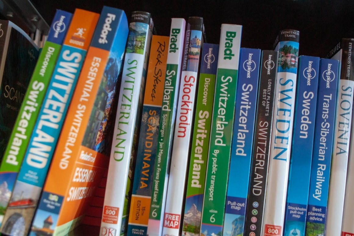A wide variety of travel guidebooks at a bookstore or library.