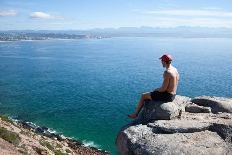 Garden Route travel guide cover image of Chris overlooking Plettenberg Bay from Robberg Peninsula.