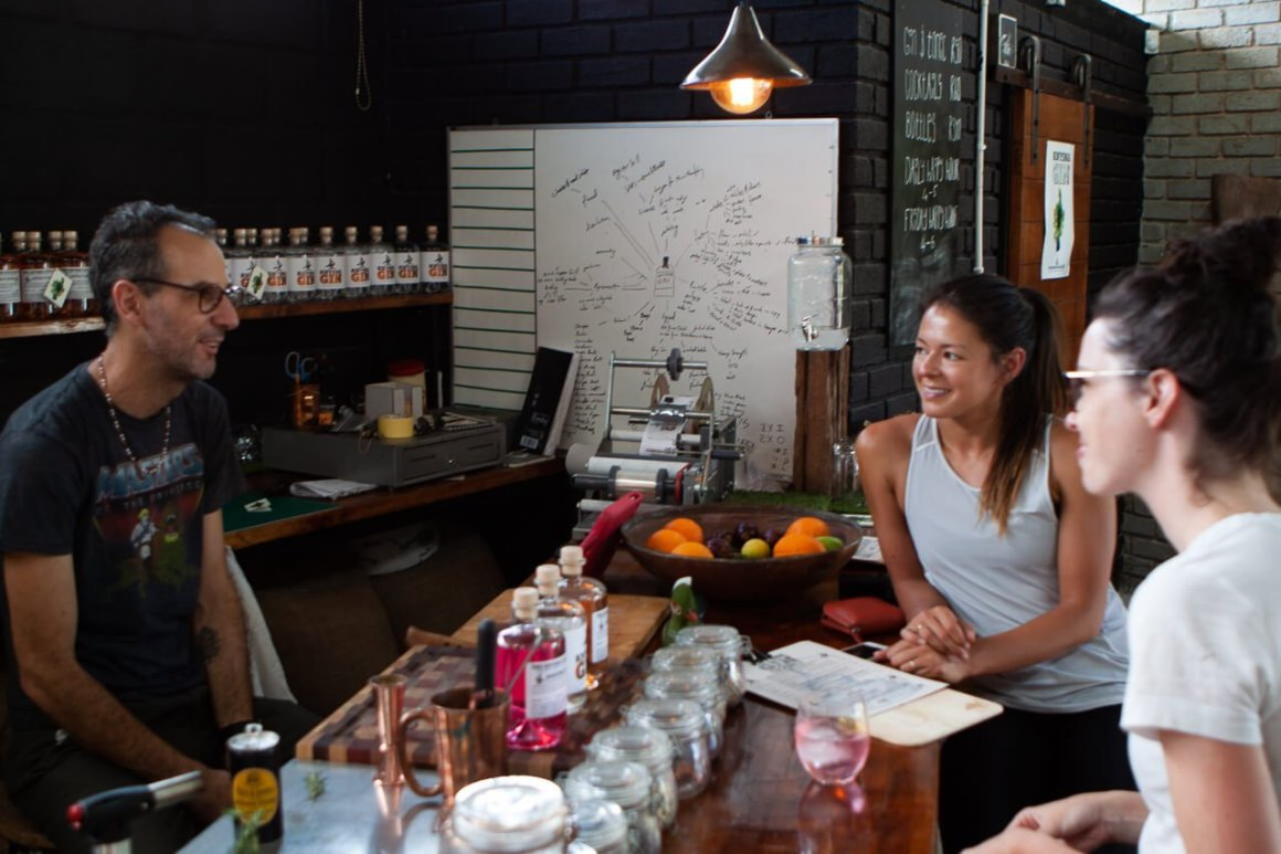 Kim and Rebecca tasting gin and listening to owner Rion's story from Knysna Gin.