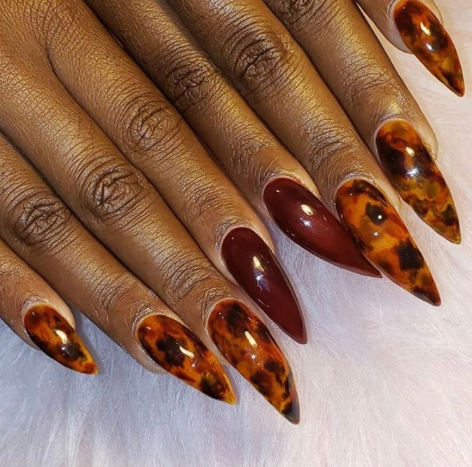 Orange and plum colored marble design stiletto acrylic nails