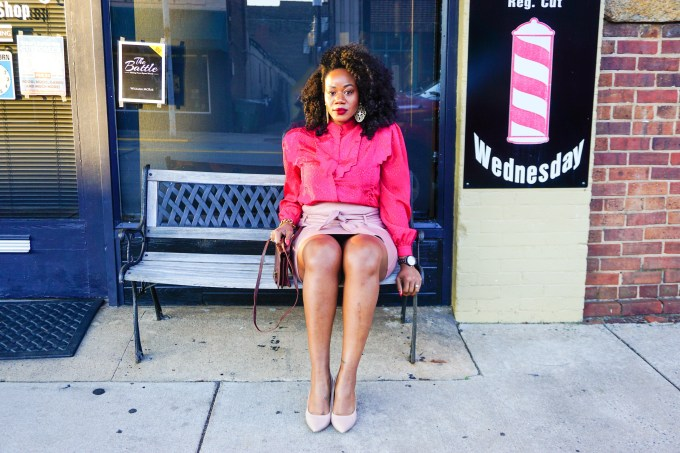 Woman in a pink shirt sitting on a bench