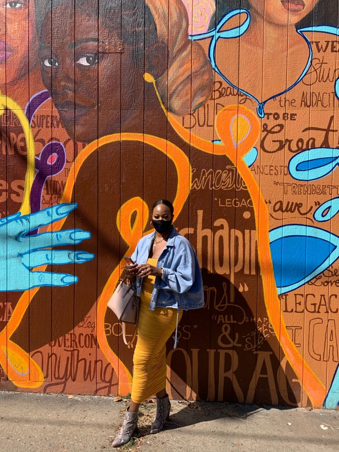 Woman in yellow dresss standing in front of a mural in Richmond, VA