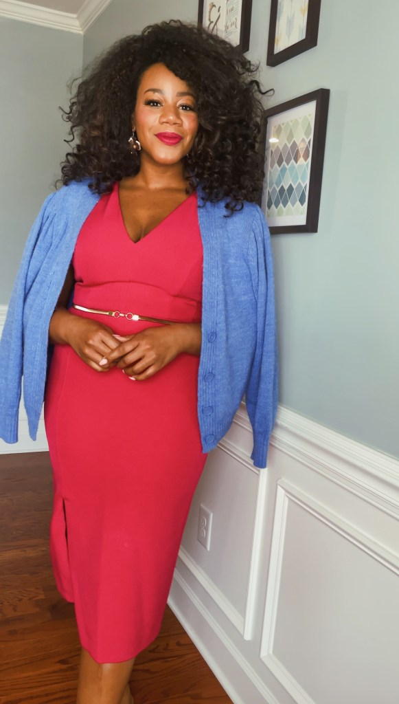 Smiling black woman with natural curly hair wearing a hot pink dress with a blue cardigan