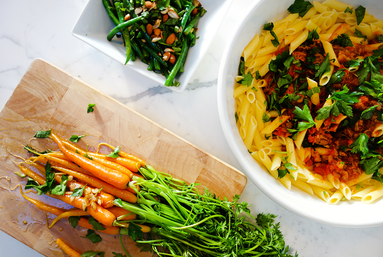 slow pulled lamb ragu on gluten free pasta with braised carrots and garlic string beans