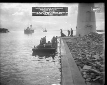 "Image shows workmen standing on a flat boat of some kind next to a pier on which the bottom of a lighthouse structure is seen. Two men in bowler hats stand on the pier while a worker in the background carries a sack over his shoulder. Two ships are seen in the distant background. Label on the original photograph reads, ""Improving St. Marys River, Michigan. New lock and canal. West Canal. Diver placing canvas cover and sandbag toe around new West Center Pier. June 12, 1911."