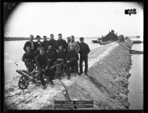"Fourteen men pose for a group photograph while standing on a dike in the Hay Lake Channel. A label on the original photograph reads ""October 27, 1889. Middle Neebish, Hay Lake Channel. Dike from Lower End."""