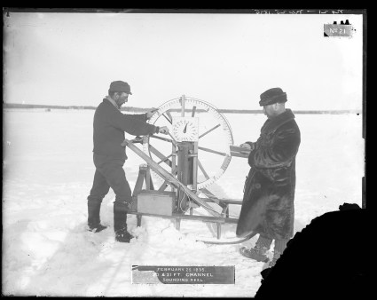"Two men in fur coats and hats use a sounding reel on an iced-over, snow-covered channel. The label includes the date February 25, 1895, and caption ""20 & 21 ft. channel. Sounding Reel."" Bottom right corner of original photograph is missing due to emulsion flaking."