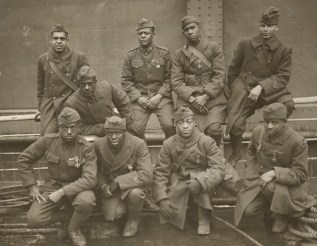 "Decorated soldiers of the 369th return home with their French Croix de Guerre awards. Front Row: Private Ed ""Eagle Eye"" Williams, Corporal Herbert ""Lamp Light"" Taylor, Private Leon Fraitor, Private Ralph ""Kid Hawk"" Hawkins. Back Row: Sergeant H.D. Prinas, Sergeant Dan Storms, Private Joe ""Kid Woney"" Williams, Private Alfred ""Kid Buck"" Hanley, and Corporal T.W. Taylor. Local Identifier, 165-WW-127-8."