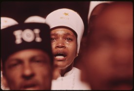 """Religious Fervor is Mirrored on the Face of a Black Muslim Woman, One of Some 10,000 Listening to Elijah Muhammad Deliver His Annual Savior's Day Message In Chicago, the City is Headquarters for the Black Muslims, Their $75 Million Empire Includes a Mosque Newspaper, University, Restaurants, Real Estate, Bank and Variety of Retail Stores, Muhammad Died February 25, 1975."" Date: 03/1974 - Photographer: John H. White (Image ID: 412-DA-13792)"
