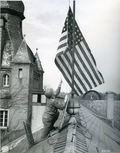 "111-SC-231596 ""1st/Sgt. David G. Lemkowitz...battalion adjutant 505th Parachute Infantry Regiment, 82nd Airborne Division, U.S. 15th Army raises American flag atop 17th century castle somewhere in Germany..."" 04/12/45"