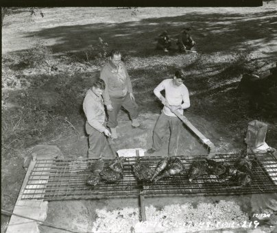 "(Local Identifier: 111-SC-171924) ""John P. Bienkieqics, Kerny, NJ, Capt. Joe E. Moore Seattle, Washington, and Pfc. Howard F. Storie, Shawnee, Oklahoma, went on a wild boar hunt. The meat is being barbecued. French Morocco, North Africa 01/19/1943."""